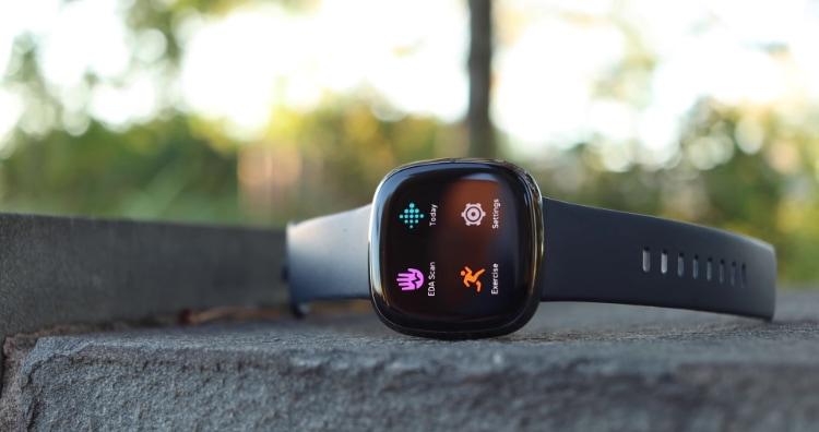 Black Fitbit Sense showing apps on pavement