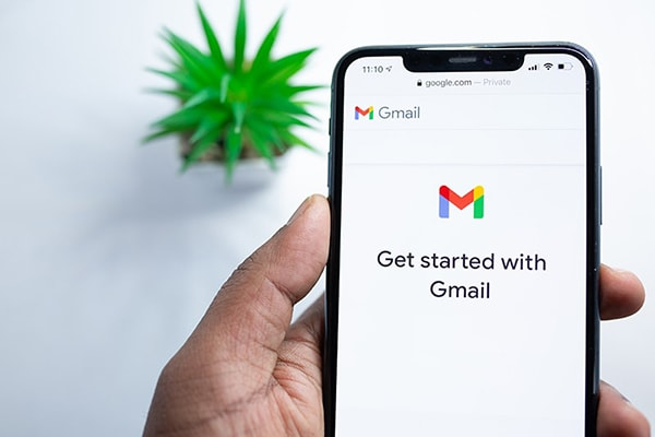 Person holding smartphone using Gmail app