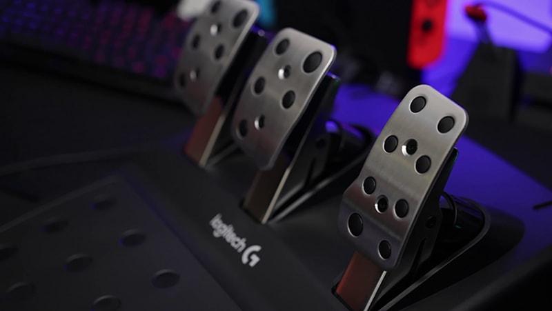 Black Logitech G920 pedals near keyboard