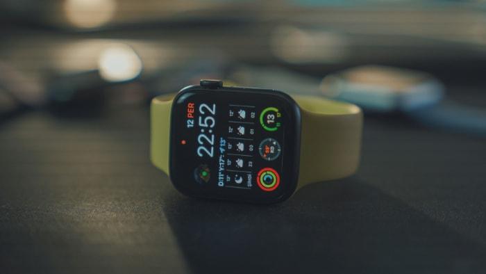 Yellow Apple Watch SE on black table