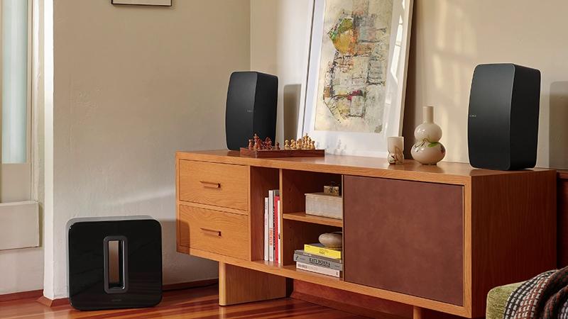 Black Sonos Sub Gen 3 near wooden rack