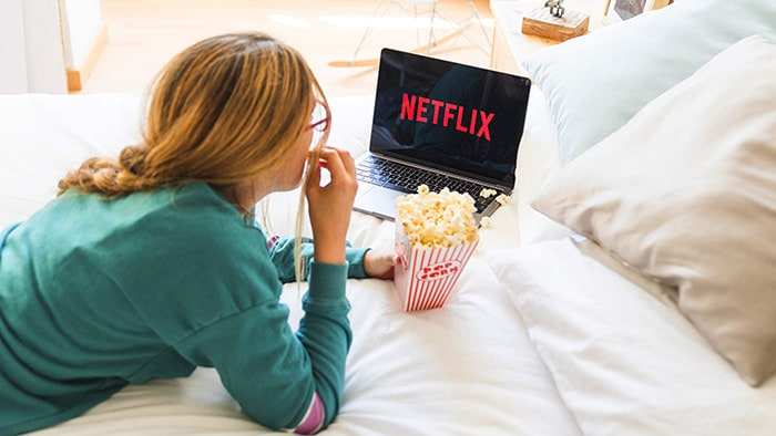 Person eating popcorn while watching netflix in bed