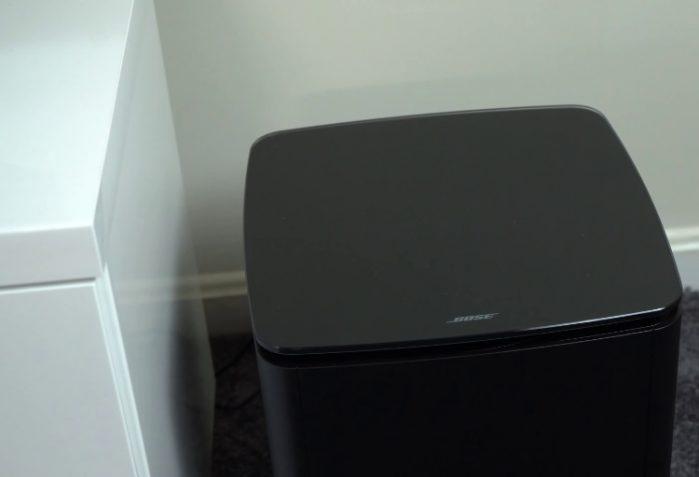 Black Bose Bass Module 700 near white cabinet
